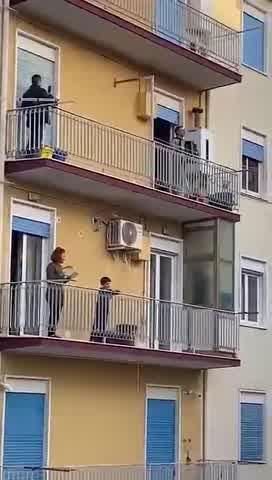 Italianos cantan con instrumentos desde sus balcones en cuarentena